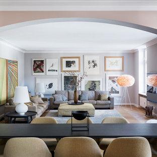 Modelo de salón cerrado, tradicional renovado, de tamaño medio, sin chimenea, con paredes grises, suelo de madera clara y televisor colgado en la pared