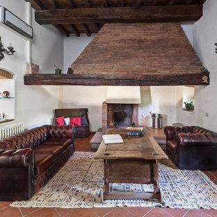 Foto di un grande soggiorno in campagna con pareti bianche, pavimento in terracotta, camino classico e cornice del camino in mattoni