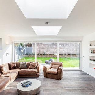 Großes Kolonialstil Wohnzimmer mit weißer Wandfarbe, dunklem Holzboden und Wand-TV in Dortmund