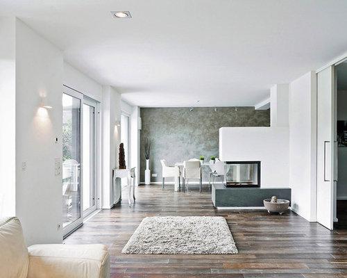 weiße Wohnküche, schwarzes Sofa und lila Akzente