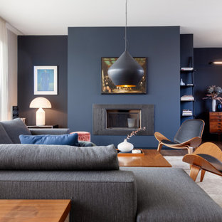 Foto di un grande soggiorno contemporaneo aperto con sala formale, pareti blu, camino classico, cornice del camino in metallo, nessuna TV e pavimento marrone