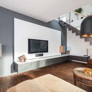 Пример оригинального дизайна: изолированная гостиная комната среднего размера в современном стиле с белыми стенами, полом из бамбука, телевизором на стене и коричневым полом без камина