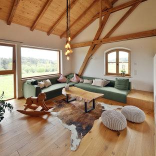 Offenes Landhausstil Wohnzimmer mit weißer Wandfarbe, braunem Holzboden, braunem Boden, freigelegten Dachbalken, gewölbter Decke und Holzdecke in München