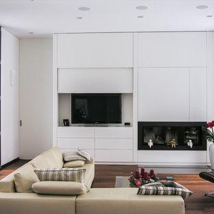 Modernes Wohnzimmer mit weißer Wandfarbe, braunem Holzboden, Gaskamin, verstecktem TV und braunem Boden in Frankfurt am Main