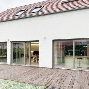 シュトゥットガルトの中くらいのモダンスタイルのおしゃれなオープンリビング (白い壁、セラミックタイルの床、コーナー設置型暖炉、漆喰の暖炉まわり、壁掛け型テレビ、ベージュの床) の写真