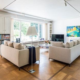 Imagen de biblioteca en casa contemporánea, de tamaño medio, con paredes blancas, suelo de madera en tonos medios y televisor independiente