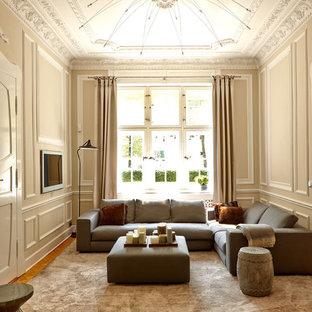 Großes, Repräsentatives, Abgetrenntes Klassisches Wohnzimmer ohne Kamin mit beiger Wandfarbe, Wand-TV und braunem Holzboden in Berlin