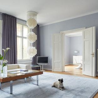 Großes, Abgetrenntes Klassisches Wohnzimmer ohne Kamin mit braunem Holzboden, freistehendem TV und lila Wandfarbe in Köln