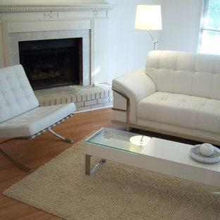 アトランタの中くらいのコンテンポラリースタイルのおしゃれなオープンリビング (白い壁、ラミネートの床、標準型暖炉、レンガの暖炉まわり、コーナー型テレビ、茶色い床) の写真