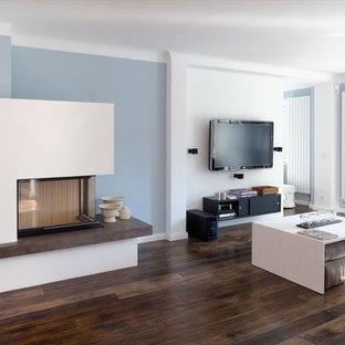 ハンブルクのコンテンポラリースタイルのおしゃれなファミリールーム (青い壁、濃色無垢フローリング、コーナー設置型暖炉、壁掛け型テレビ、漆喰の暖炉まわり) の写真