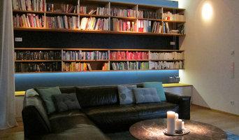 Raumhohe Bücherwand im Wohnraum am Abend