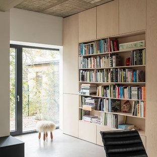 Offene, Mittelgroße, Fernseherlose Moderne Bibliothek mit weißer Wandfarbe, Betonboden und grauem Boden in Berlin