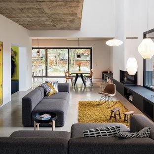 Mittelgroßes, Repräsentatives, Fernseherloses Modernes Wohnzimmer im Loft-Style mit weißer Wandfarbe, Betonboden, Kamin, grauem Boden und verputztem Kaminsims in Berlin