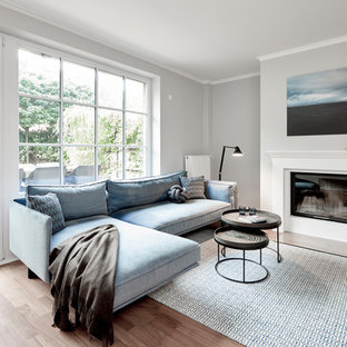 Mittelgroßes, Abgetrenntes Modernes Wohnzimmer mit grauer Wandfarbe, gebeiztem Holzboden, verputzter Kaminumrandung, braunem Boden und Kamin in Hamburg