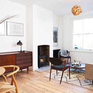 ロンドンの中くらいのミッドセンチュリースタイルのおしゃれなオープンリビング (白い壁、無垢フローリング、薪ストーブ、レンガの暖炉まわり) の写真