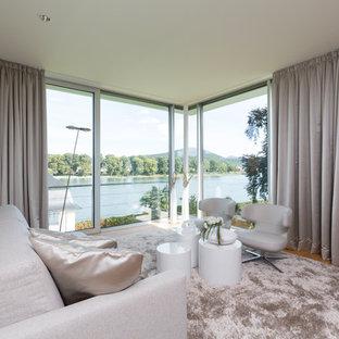 Mittelgroßes, Fernseherloses, Abgetrenntes Modernes Wohnzimmer ohne Kamin mit weißer Wandfarbe, braunem Holzboden und braunem Boden in Köln