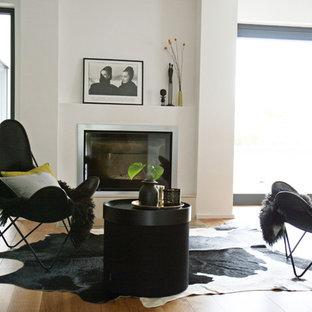Ejemplo de sala de estar actual, pequeña, sin televisor, con paredes blancas, suelo de madera en tonos medios, chimenea tradicional, marco de chimenea de yeso y suelo marrón