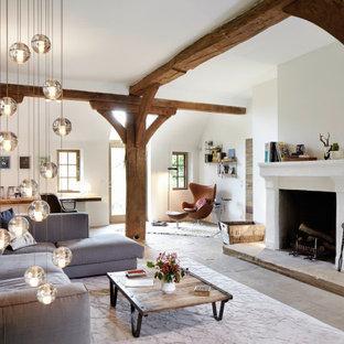 Offenes Country Wohnzimmer mit weißer Wandfarbe, Kamin, grauem Boden und freigelegten Dachbalken in Hamburg