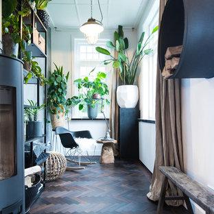 Abgetrenntes Modernes Wohnzimmer mit weißer Wandfarbe, dunklem Holzboden, Kaminofen und braunem Boden