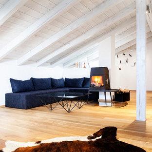 Abgetrenntes, Großes, Repräsentatives Skandinavisches Wohnzimmer mit weißer Wandfarbe, hellem Holzboden, Kaminofen, Kaminumrandung aus Metall, verstecktem TV und braunem Boden in München