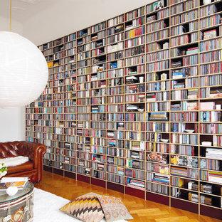 Cette image montre un grand salon avec une bibliothèque ou un coin lecture design fermé avec un mur blanc et un sol en bois brun.