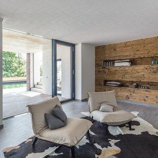 Modernes Wohnzimmer ohne Kamin mit weißer Wandfarbe, braunem Holzboden und braunem Boden in Sonstige