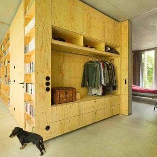 Foto de biblioteca en casa abierta, contemporánea, pequeña, sin chimenea y televisor, con paredes grises y suelo de cemento
