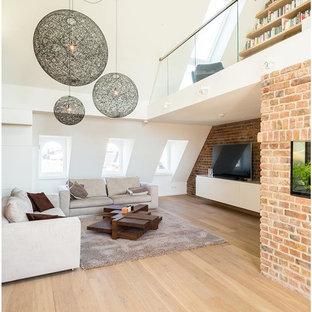 Geräumige Industrial Bibliothek ohne Kamin, im Loft-Stil mit weißer Wandfarbe, hellem Holzboden, freistehendem TV und braunem Boden in Köln