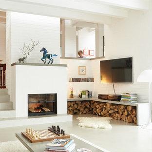 Imagen de sala de estar abierta, contemporánea, de tamaño medio, con paredes blancas, chimenea tradicional, televisor colgado en la pared y marco de chimenea de yeso