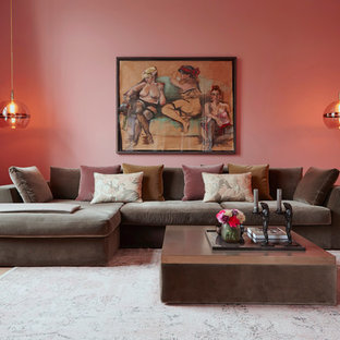 Design ideas for a traditional living room in Hamburg with medium hardwood floors, brown floor and pink walls.