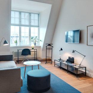 Diseño de salón cerrado, escandinavo, de tamaño medio, sin chimenea, con paredes blancas, suelo de madera en tonos medios y televisor colgado en la pared