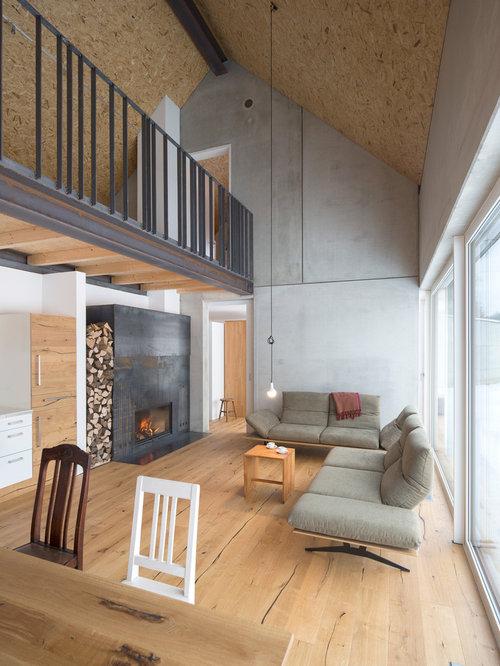Offenes, Mittelgroßes Industrial Wohnzimmer Mit Grauer Wandfarbe, Hellem  Holzboden, Gaskamin Und Kaminsims Aus