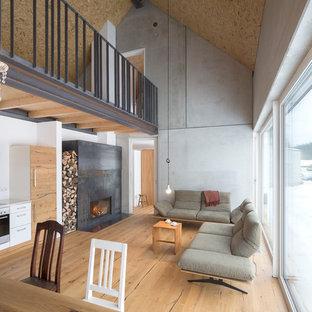 Offenes, Mittelgroßes Industrial Wohnzimmer mit grauer Wandfarbe, hellem Holzboden, Kaminumrandung aus Metall und braunem Boden in Sonstige