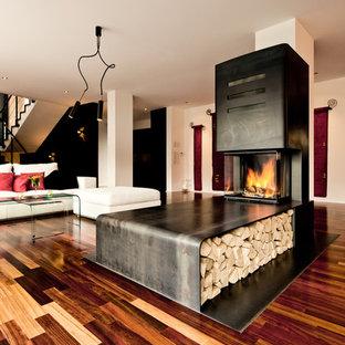 Réalisation d'une grande salle de séjour urbaine avec un sol en bois brun, une cheminée d'angle et un manteau de cheminée en métal.