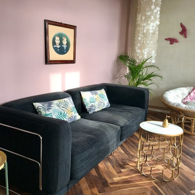 Inspiration for a small eclectic open concept medium tone wood floor and brown floor family room remodel in Berlin with multicolored walls and no fireplace