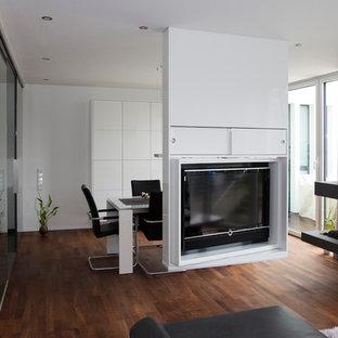 ケルンの大きいコンテンポラリースタイルのおしゃれな独立型ファミリールーム (白い壁、濃色無垢フローリング、両方向型暖炉、コンクリートの暖炉まわり、内蔵型テレビ、茶色い床) の写真