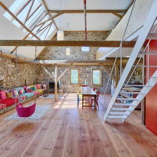 Großes, Repräsentatives, Offenes Stilmix Wohnzimmer mit grauer Wandfarbe, braunem Holzboden, freistehendem TV und beigem Boden in Sonstige