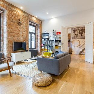 Modelo de sala de estar urbana, grande, sin chimenea, con paredes blancas y suelo de madera en tonos medios