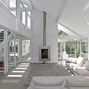 Immagine di un grande soggiorno design stile loft con pareti bianche, pavimento con piastrelle in ceramica, stufa a legna, nessuna TV e pavimento grigio