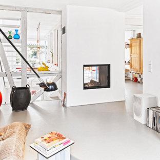 Esempio di un soggiorno design aperto e di medie dimensioni con pareti bianche, pavimento in linoleum, camino bifacciale, cornice del camino in intonaco e TV autoportante