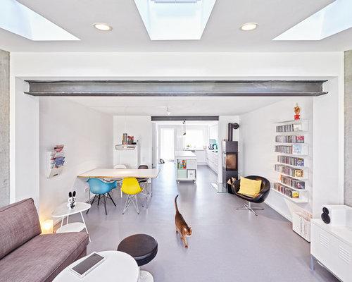 Großes, Offenes Modernes Wohnzimmer Mit Weißer Wandfarbe, Betonboden,  Kaminofen Und Freistehendem TV In