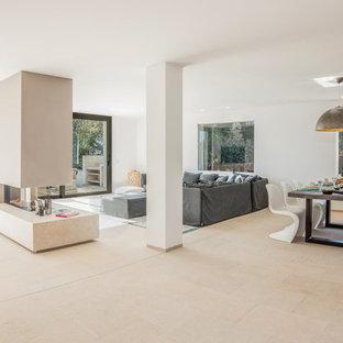 Ispirazione per un grande soggiorno moderno aperto con pareti beige, pavimento in marmo, camino classico, cornice del camino in cemento e TV a parete