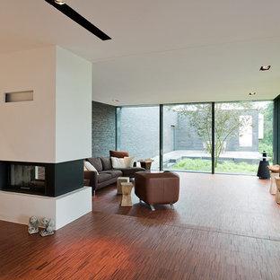 Großes, Repräsentatives, Offenes Modernes Wohnzimmer Mit Weißer Wandfarbe, Dunklem  Holzboden Und Tunnelkamin In
