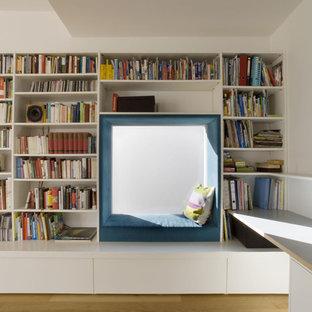 На фото: гостиная комната среднего размера в современном стиле с белыми стенами, паркетным полом среднего тона и библиотекой без камина с