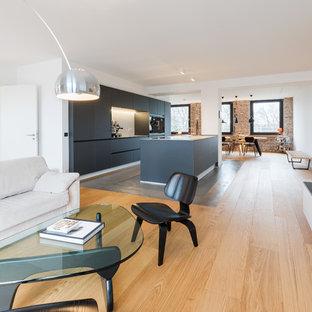 Repräsentatives, Geräumiges Industrial Wohnzimmer im Loft-Stil mit weißer Wandfarbe, braunem Holzboden, Gaskamin, verputzter Kaminumrandung, Wand-TV und braunem Boden in Essen