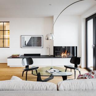 Mittelgroßes, Offenes Modernes Wohnzimmer mit weißer Wandfarbe, hellem Holzboden, Gaskamin, Wand-TV, braunem Boden und verputzter Kaminumrandung in Essen