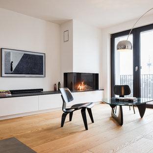 Réalisation d'une grande salle de séjour urbaine ouverte avec un sol en bois clair, une cheminée ribbon, un manteau de cheminée en plâtre, un téléviseur fixé au mur, un sol marron et un mur blanc.