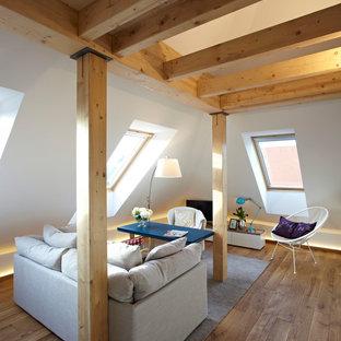 Immagine di un piccolo soggiorno minimal con pareti bianche, pavimento in legno massello medio, nessun camino e TV autoportante