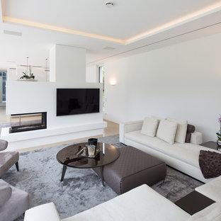 エッセンの中サイズのコンテンポラリースタイルのおしゃれなファミリールーム (白い壁、カーペット敷き、両方向型暖炉、漆喰の暖炉まわり) の写真