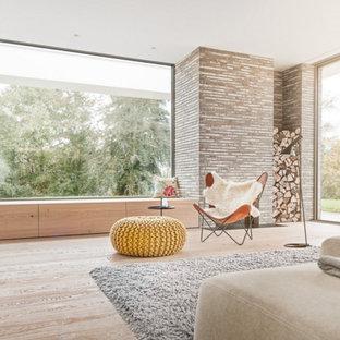 Diseño de sala de estar actual, de tamaño medio, con paredes marrones y suelo de madera clara